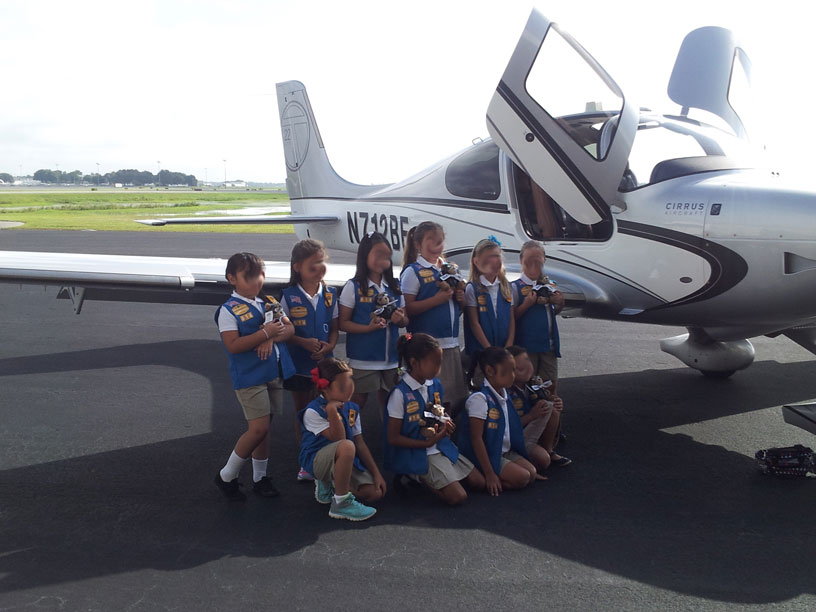 Image of Girl Scouts group infront of Cirrus airplane