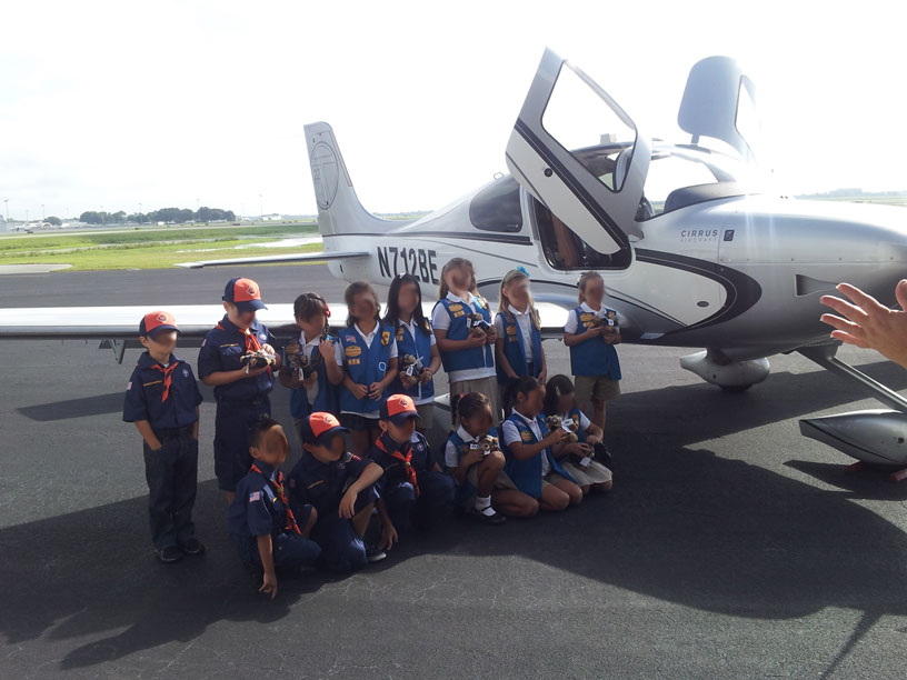 Image of Girl Scouts and Boy Scouts group in front of Cirrus airplane