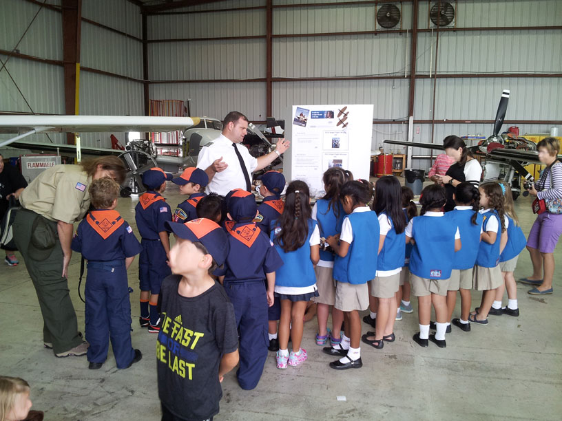Image of Boy and Girl Scouts talking with a pilot