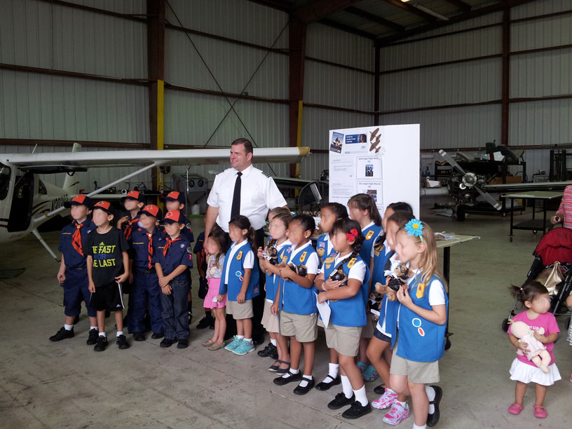 Image of Boy and Girl scouts posing with pilot for pictures