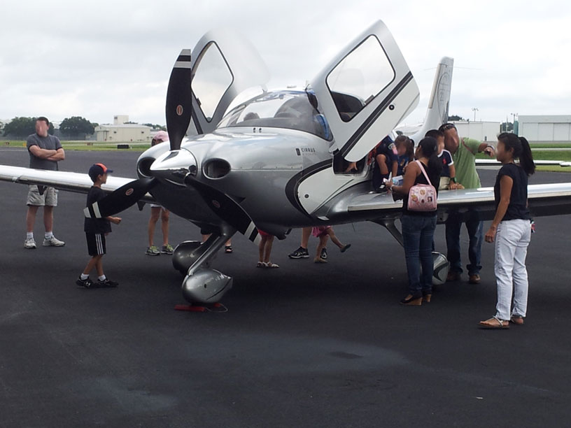 Image of group looking at Cirrus airplane